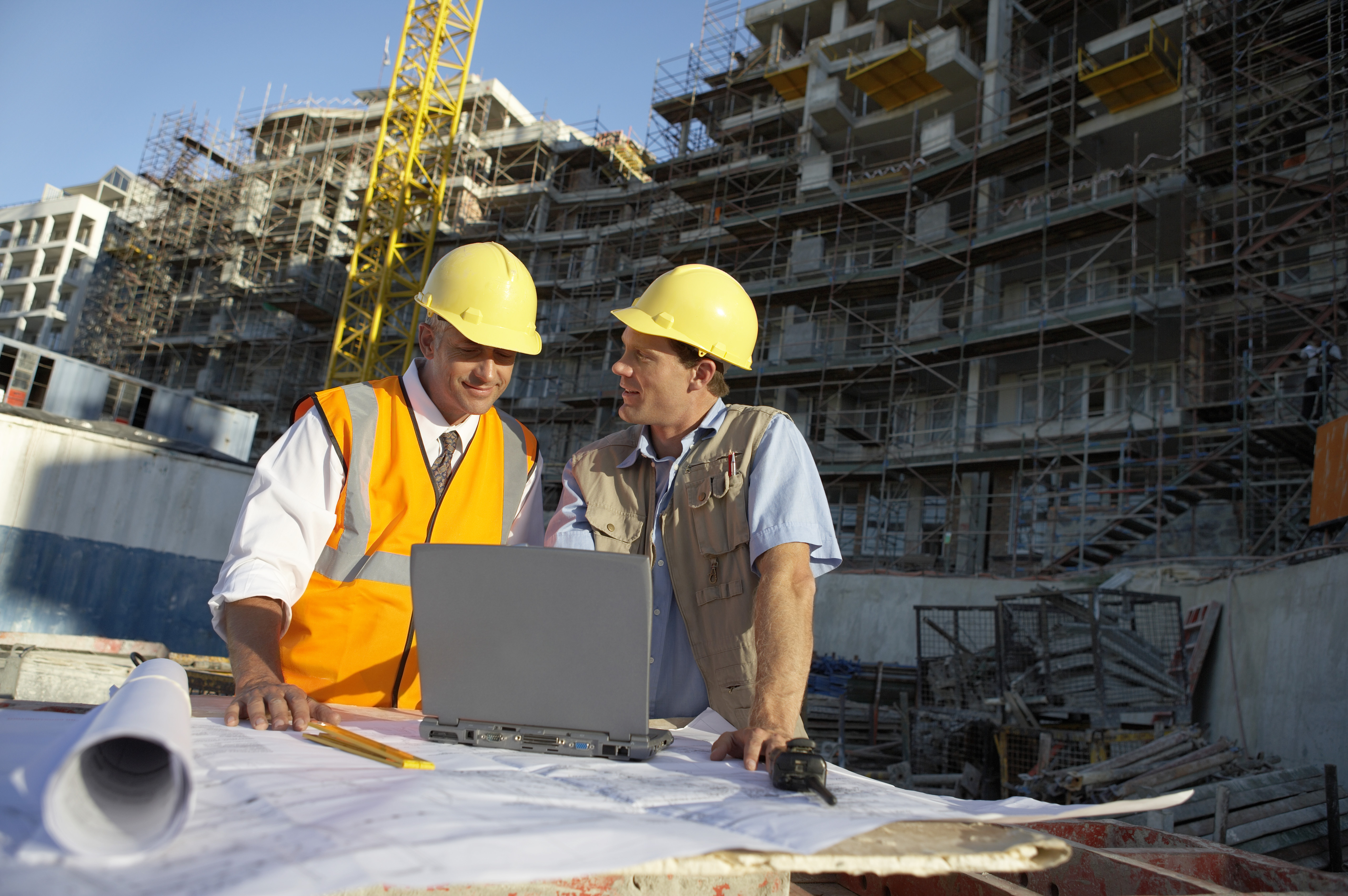 how project photos effect a construction company s brand brand two men wearing hard hats looking at a laptop computer on a building site